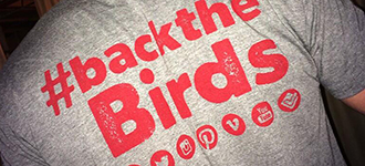 Back of male student's tshirt that says '#BacktheBirds'