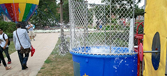 Action shot of someone falling into the dunk tank at Festival ISU