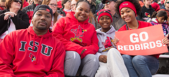 Family dressed in ISU gear sitting in stands at football game with sign that says 'Go Redbirds'