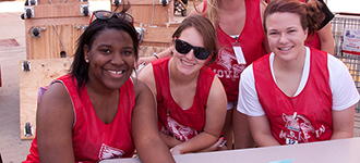 Three female student helpers sitting at table outside during move-in